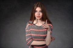 Dziewczyn przedstawień nieufność przeciw ciemnemu tłu obrazy stock