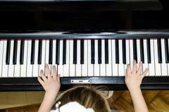 Dziewczyn ręki i fortepianowej klawiatury zakończenia widok Obrazy Stock