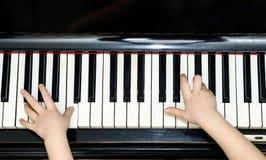 Dziewczyn ręki i fortepianowej klawiatury zakończenia widok Obraz Stock