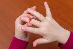 dziewczyn ręki stawiają dalej złotego pierścionek z czerwonym diamentem zdjęcie royalty free