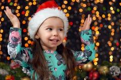 Dziewczyn ręki up w boże narodzenie dekoraci z prezentem, ciemnym tle z iluminacją i boke, zaświecają, zima wakacje pojęcie Zdjęcie Stock