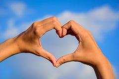 Dziewczyn ręki w kształcie miłości serce na niebieskim niebie Fotografia Stock