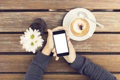 Dziewczyn ręki z pustym smartphone, filiżanką kawy i kwiatami, zdjęcia royalty free