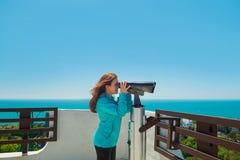 Dziewczyn spojrzenia przez teleskopu na dennym tle Obrazy Royalty Free