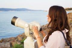 Dziewczyn spojrzenia przez teleskopu przy morzem Zdjęcie Stock