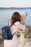 Dziewczyn spojrzenia przez teleskopu przy morzem Obrazy Stock