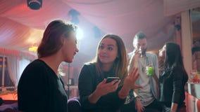 Dziewczyn spojrzenia przy ekranem laught na tle lumiere za barem odpierającym i telefon komórkowy w klubie zbiory