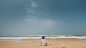 Dziewczyn spojrzenia przy oceanu obsiadaniem na piasku Fotografia Stock