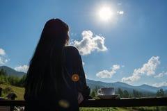 Dziewczyn spojrzenia przy ranek górami i słońcem Obok ona, na poręczu balkon, jest filiżanka kawy obrazy stock