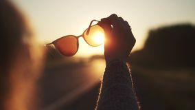 Dziewczyn spojrzenia przy słońcem przez okularów przeciwsłonecznych Kobieta chwyty w ręka okularach przeciwsłonecznych swobodny r zbiory