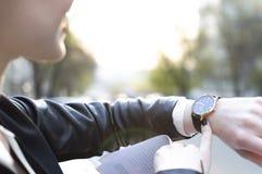 Dziewczyn spojrzenia przy zegarem słońce błyszczą w kamerze zdjęcia stock
