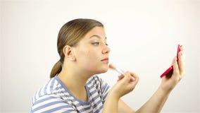 Dziewczyn spojrzenia w lustrze i pudrują jej twarz zbiory