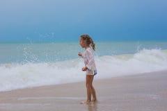 Dziewczyn spojrzenia w odległość ocean na plaży w burzy wściekać się Zdjęcie Royalty Free