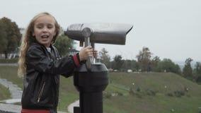 Dziewczyn spojrzenia w teleskop przy viewing miejscem zbiory
