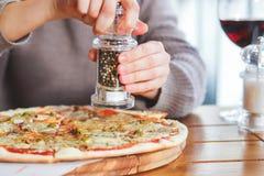 Dziewczyn sumujące pikantność na górze pizzy z mozzarellą zdjęcie royalty free