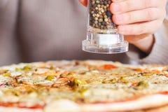 Dziewczyn sumujące pikantność na górze pizzy z mozzarellą obrazy stock