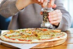 Dziewczyn sumujące pikantność na górze pizzy z mozzarella serem obrazy royalty free
