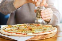 Dziewczyn sumujące pikantność na górze pizzy z mozzarella serem zdjęcie royalty free