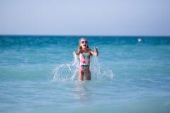 Dziewczyn sztuki przy morzem i pluśnięcia fotografia stock