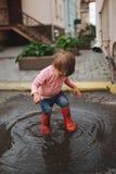 Dziewczyn sztuki w kałuży outdoors zdjęcia royalty free