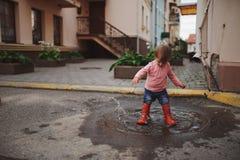Dziewczyn sztuki w kałuży outdoors obraz stock