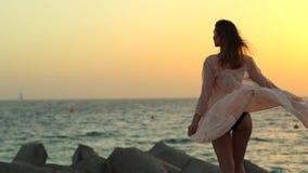 Dziewczyn sztuki z suknią przy zmierzchem na kamieniach wyrzucać na brzeg w Dubaj zbiory wideo