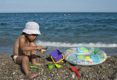 Dziewczyn sztuki z zabawkami na plaży obrazy stock