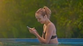 Dziewczyn Uses Smartphone w basenie one Uśmiechają się pod słońce promieni zbliżeniem zdjęcie wideo