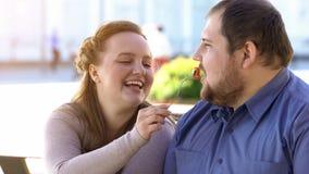 Dziewczyna żywieniowy chłopak z sałatką, para ma lunch outside, miasto data obrazy stock