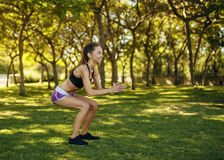 Dziewczyna ćwiczy sport robi kucnięciu w parku Zdjęcia Royalty Free