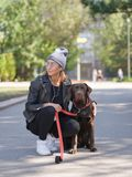 Dziewczyna ściska jej psa podczas gdy kucający psa fotografia stock