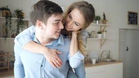 Dziewczyna śmia się całowanie mężczyzny w kuchni skakał na facetów ramionach zdjęcie wideo