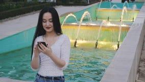 Dziewczyna śmia się włosianego używa smartphone i podrzuca zbiory