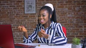 Dziewczyna śmiesząca patrzeć jej czerwonego notatnika i trzymać jej głowę zaskakująca podczas gdy siedzący przy biurkiem w ceglan