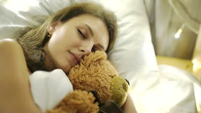 Dziewczyna śpi w łóżku z zabawką misia 4k 20s zdjęcie wideo
