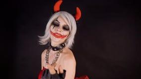 Dziewczyna świętuje Halloween z płonącymi baniami, zabawę, raduje się Dosyć plciowa czarcia kobieta skinie ręką, skinie zbiory wideo