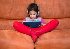 Dziewczyna bawić się pastylka komputer osobistego z hełmofonami Zdjęcia Royalty Free