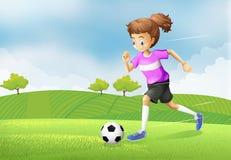 Dziewczyna bawić się piłkę nożną przy polem Zdjęcia Royalty Free