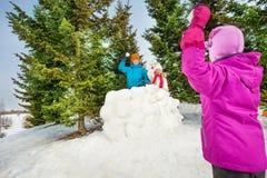 Dziewczyna bawić się snowball grę z jej przyjaciółmi Obrazy Royalty Free