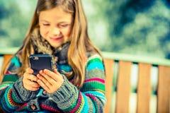 Dziewczyna Bawić się telefon komórkowego Obrazy Royalty Free