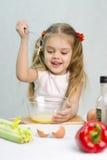 Dziewczyna bawić się w kucbarskim kierzanki śmignięciu jajka w szklanym pucharze Zdjęcie Stock
