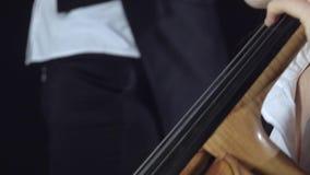 Dziewczyna bawić się wiolonczeli profesjonalnie liryczną muzykę Czarny tło z bliska zdjęcie wideo