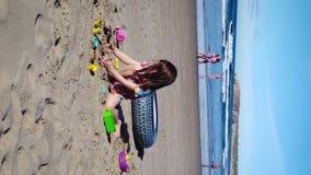 Dziewczyna bawić się z jej zabawkami na plaży zdjęcie wideo