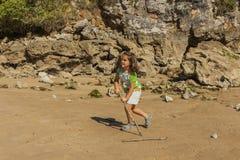 Dziewczyna bawić się z piaskiem w skalistej plaży Zdjęcie Royalty Free