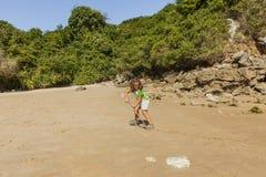 Dziewczyna bawić się z piaskiem w skalistej plaży Obraz Stock