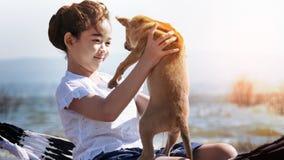 Dziewczyna bawić się z psem na hamaku Obraz Stock