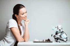 Dziewczyna bawić się z robotem w szachy Robot siedzi naprzeciw ona na stole Obrazy Stock