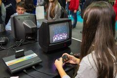 Dziewczyna bawić się z rocznika Atari Pac mężczyzna przy gra tygodniem 2015 Zdjęcia Stock