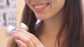 Dziewczyna bawi się z wiercipięta kądziołkiem podczas gdy siedzący w krześle Młoda atrakcyjna kobieta patrzeje kamerę i ono uśmie zbiory