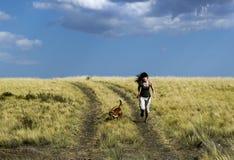 Dziewczyna bieg z psem na wiejskiej drodze w lato naturze Obraz Royalty Free